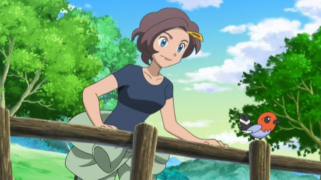 Pokémon X & Y anime screenshot of Grace, a woman with short brown hair with a sweater tied around her waist, leaning on a fence smiling next to a perched Fletchling.