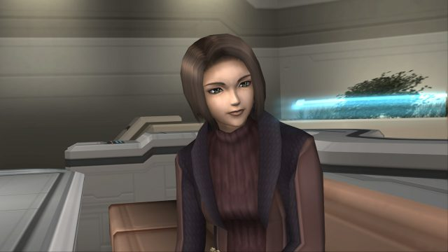 Xenosaga screenshot of Juli Mizrahi, a woman with short brown hairwearing a black and maroon sweater and vest, in a futuristic common room.
