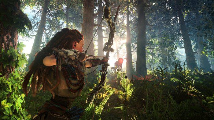 Aloy lies in wait as a mechanical beast walks through the forest toward her.