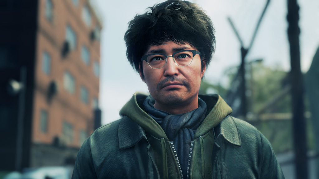 A man with fluffy hair and glasses stares in the camera's direction.