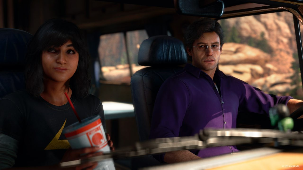 Kamala, sits in the passenger seat of a car with a large drink, slightly smiling, with Bruce behind the wheel.