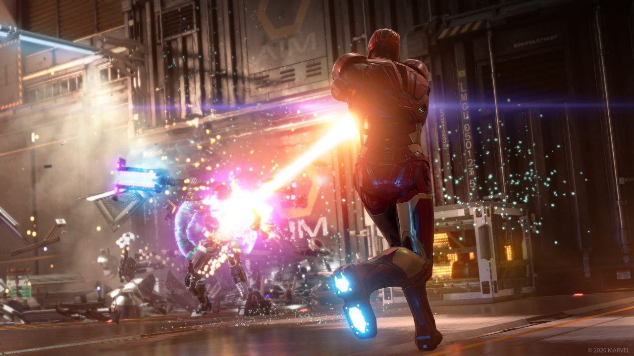 Iron Man, turned away from the viewer and in the suit, shoots a purple and orange laser at some robots in the background.