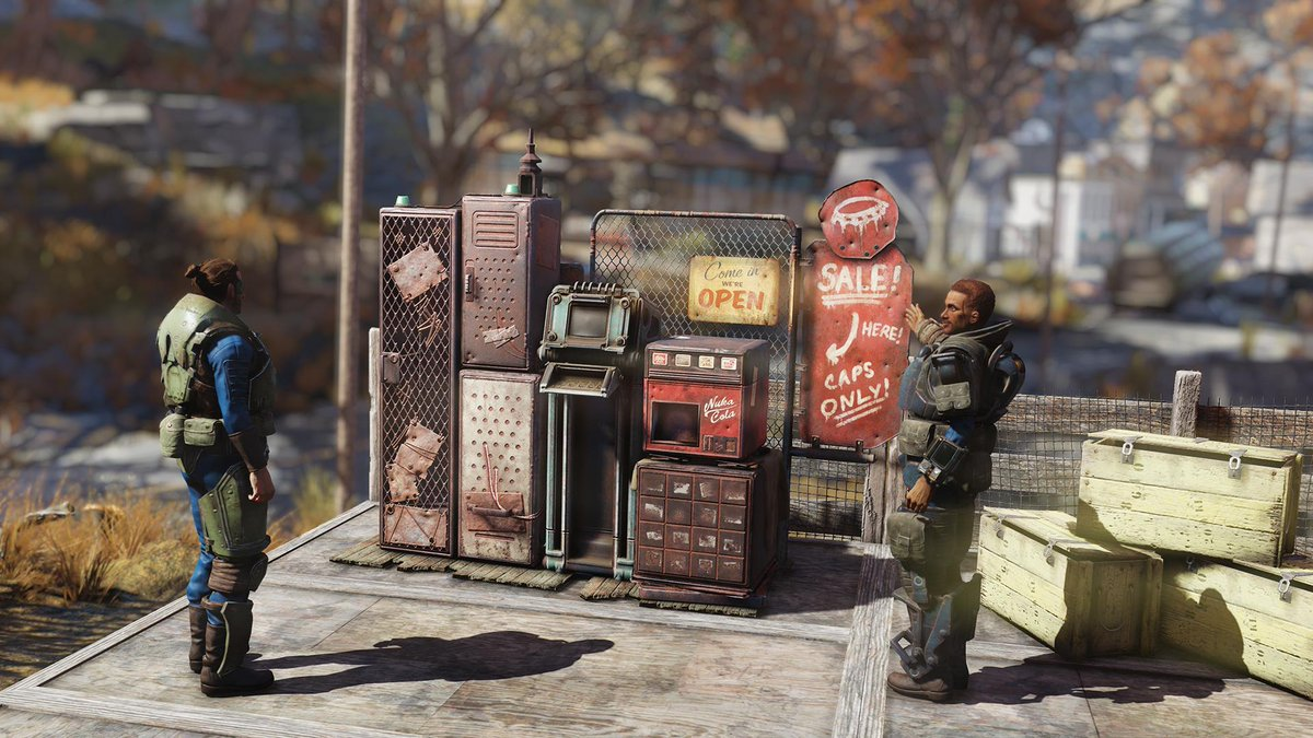 """One character on the right gestures toward a beaten up vending machine with a sign that reads """"Sale! Here! Caps only!"""" while another player character looks on."""