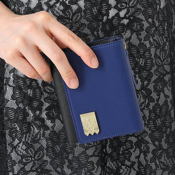 SuperGroupies Fire Emblem Three Houses Closeup of blue leather wallet being held near a black lace dress