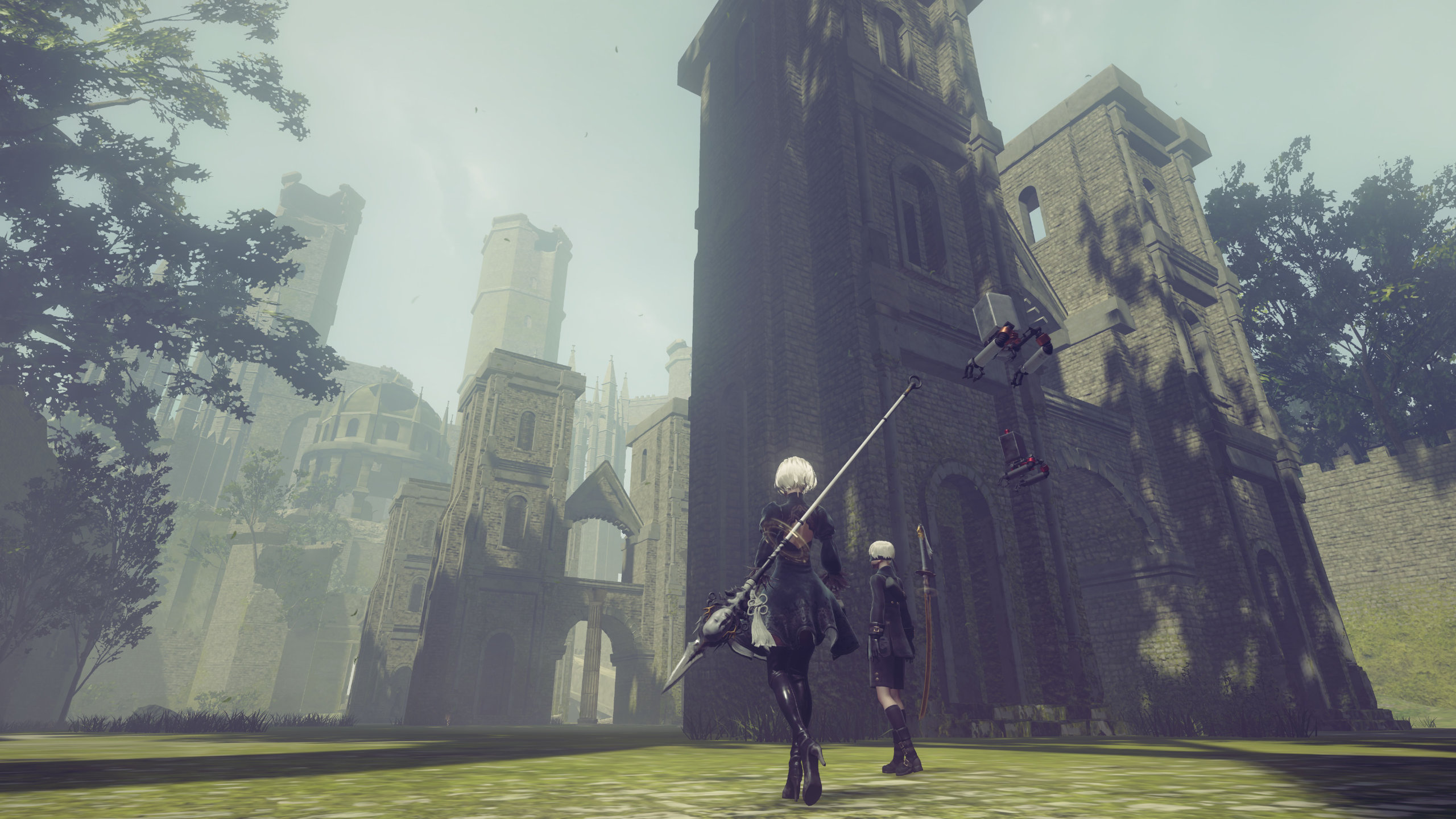 NieR: Automata screenshot of 2B and 9S in the foggy ruins of an abandoned forest castle.