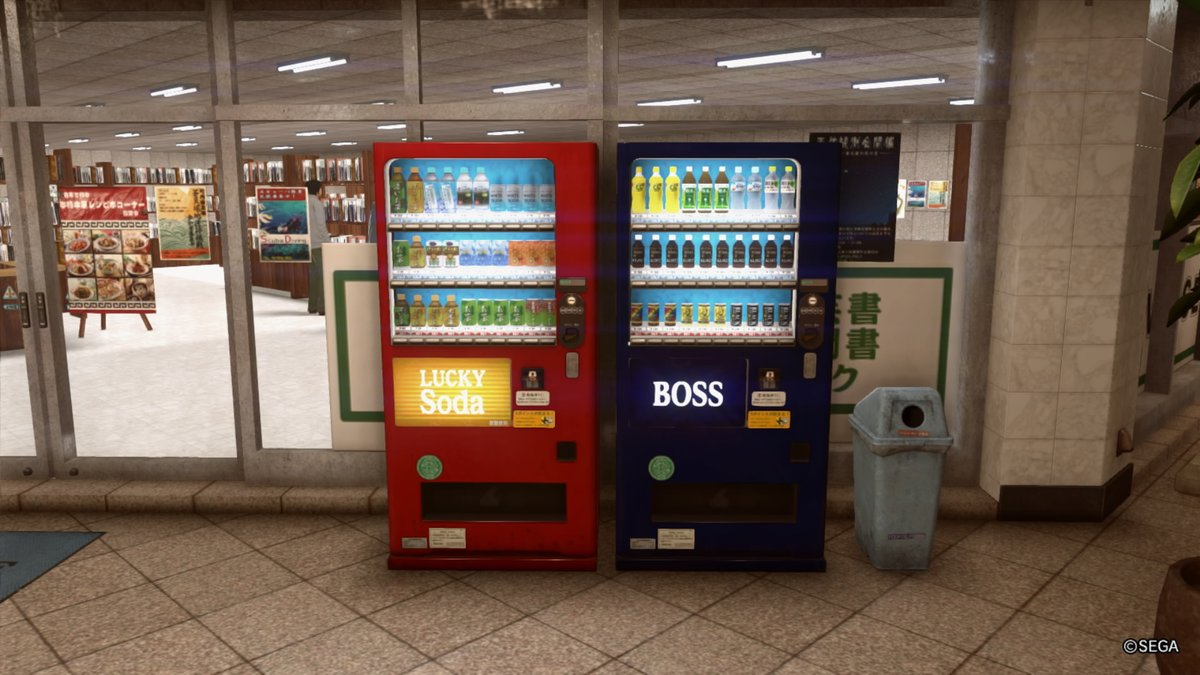 A pair of vending machines at the entry to a store: a red Lucky Soda machine on the left and closest to the door, and Boss Coffee on the right.