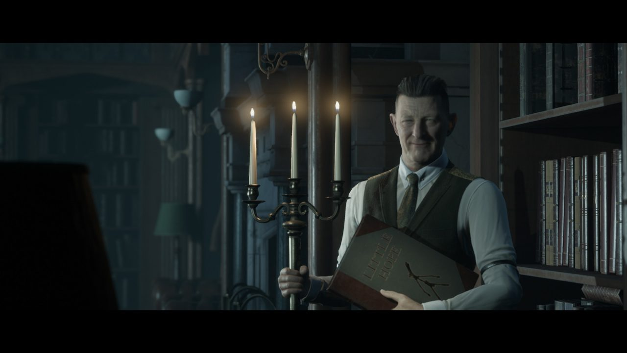A smirking man holds a large tome and candle holder in a dark library.