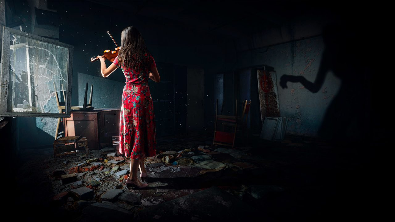 A woman in a red dress plays the violin in a dilapidated room