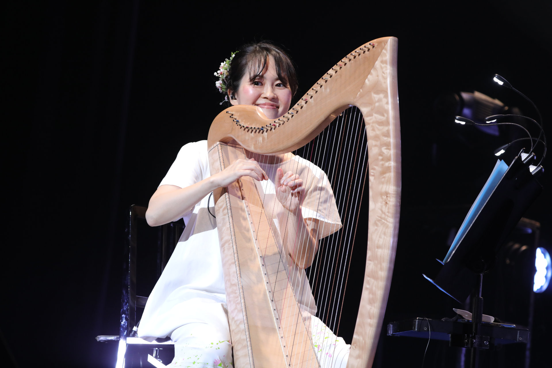 A harpist dressed all in white performs at the Chrono Cross concert.