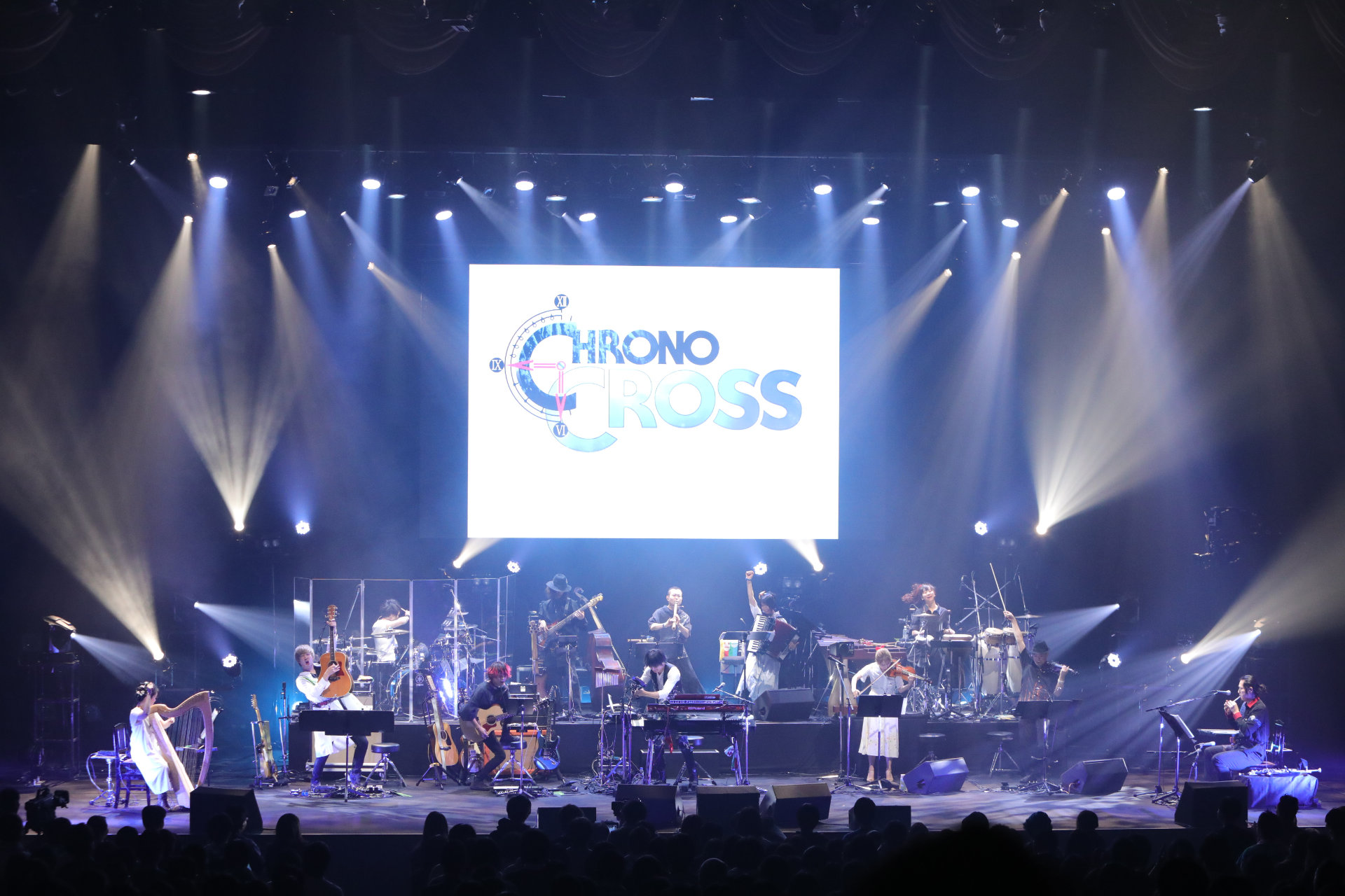 Concert photo showing the full stage of musicians performing with the Chrono Cross logo on a screen.