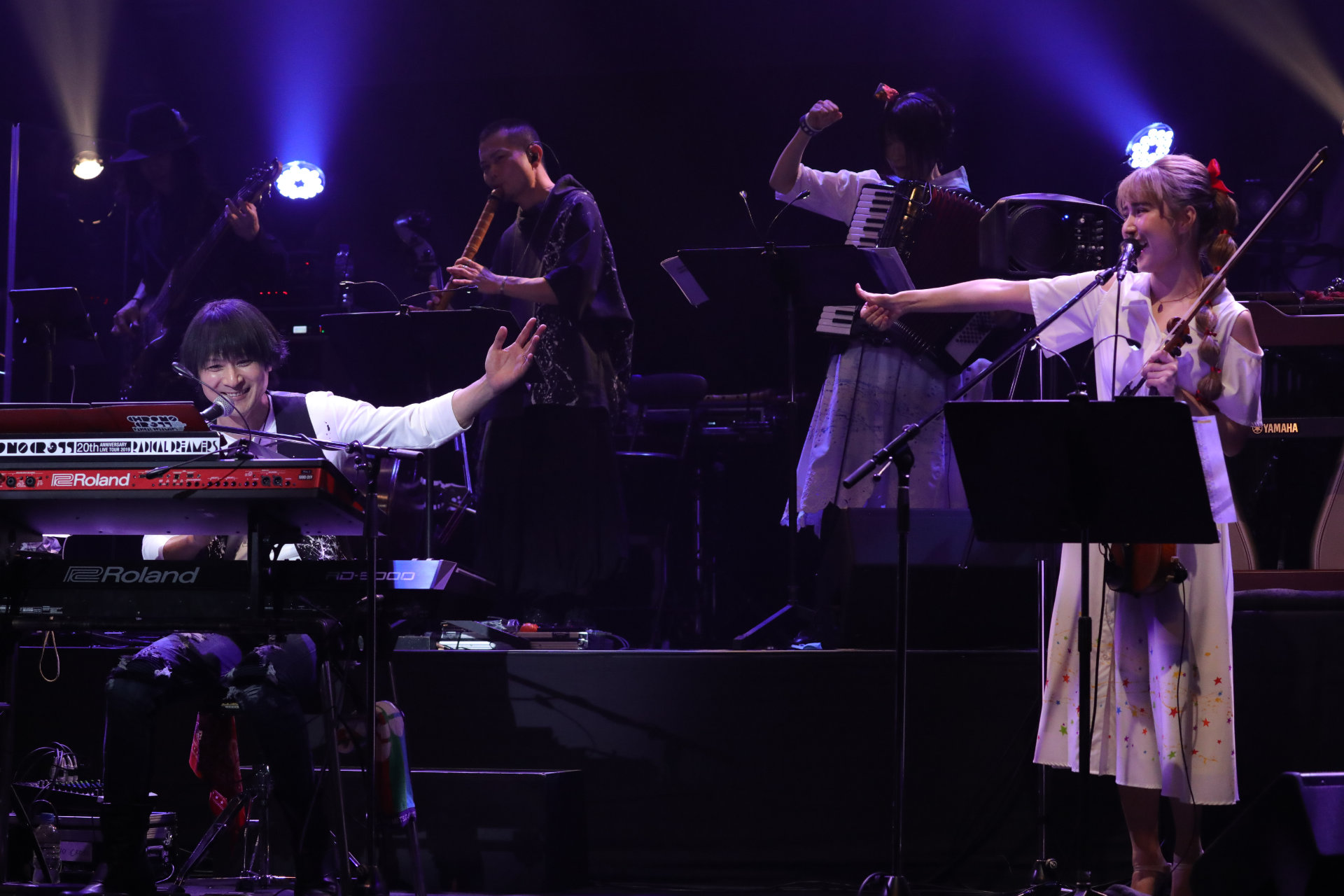 Chrono Cross concert photo of a female violinist giving composer Yasunori Mitsuda a thumbs-up while he sits at his keyboards.