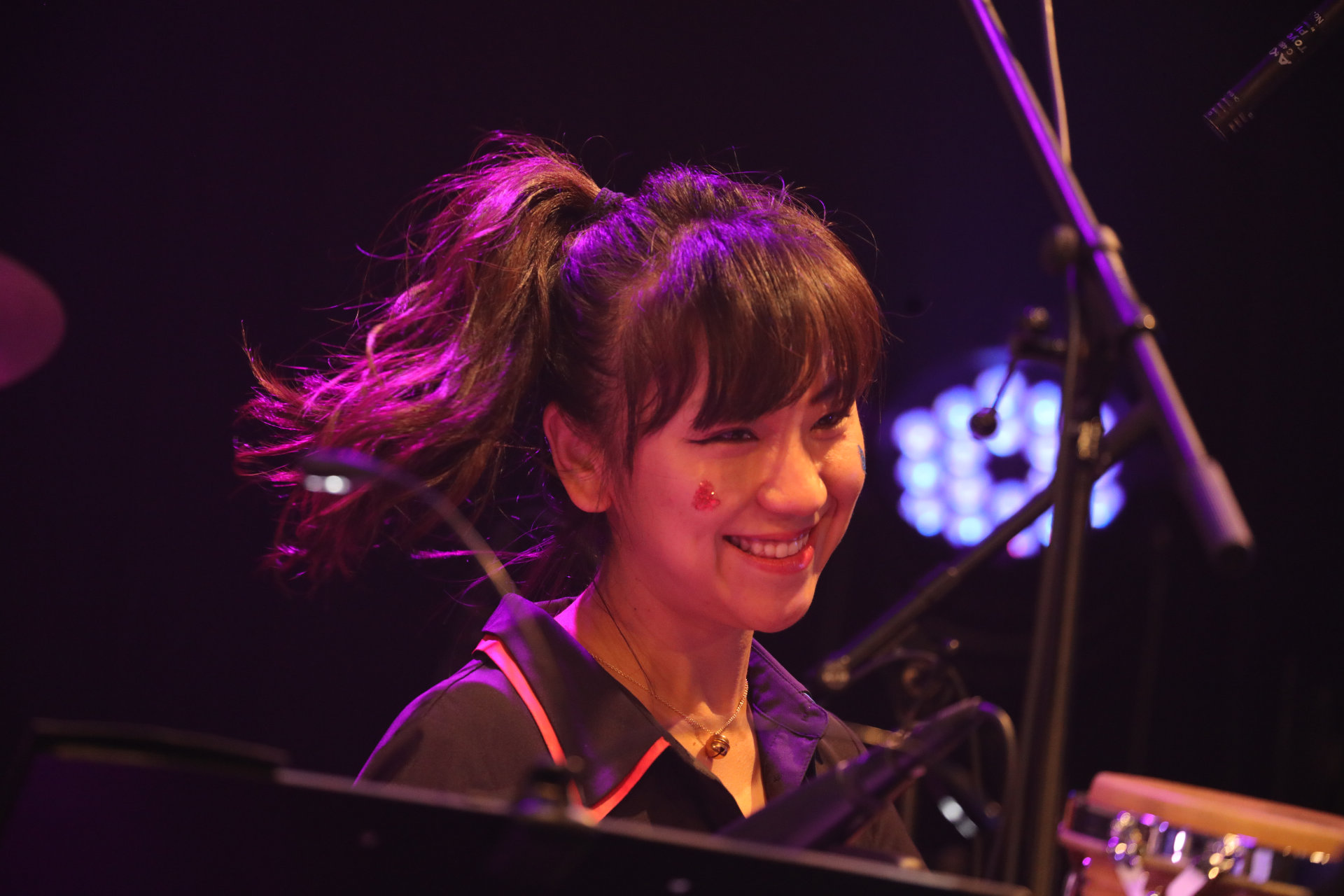 A smiling woman in the orchestra with a sparkling heart on her cheek.
