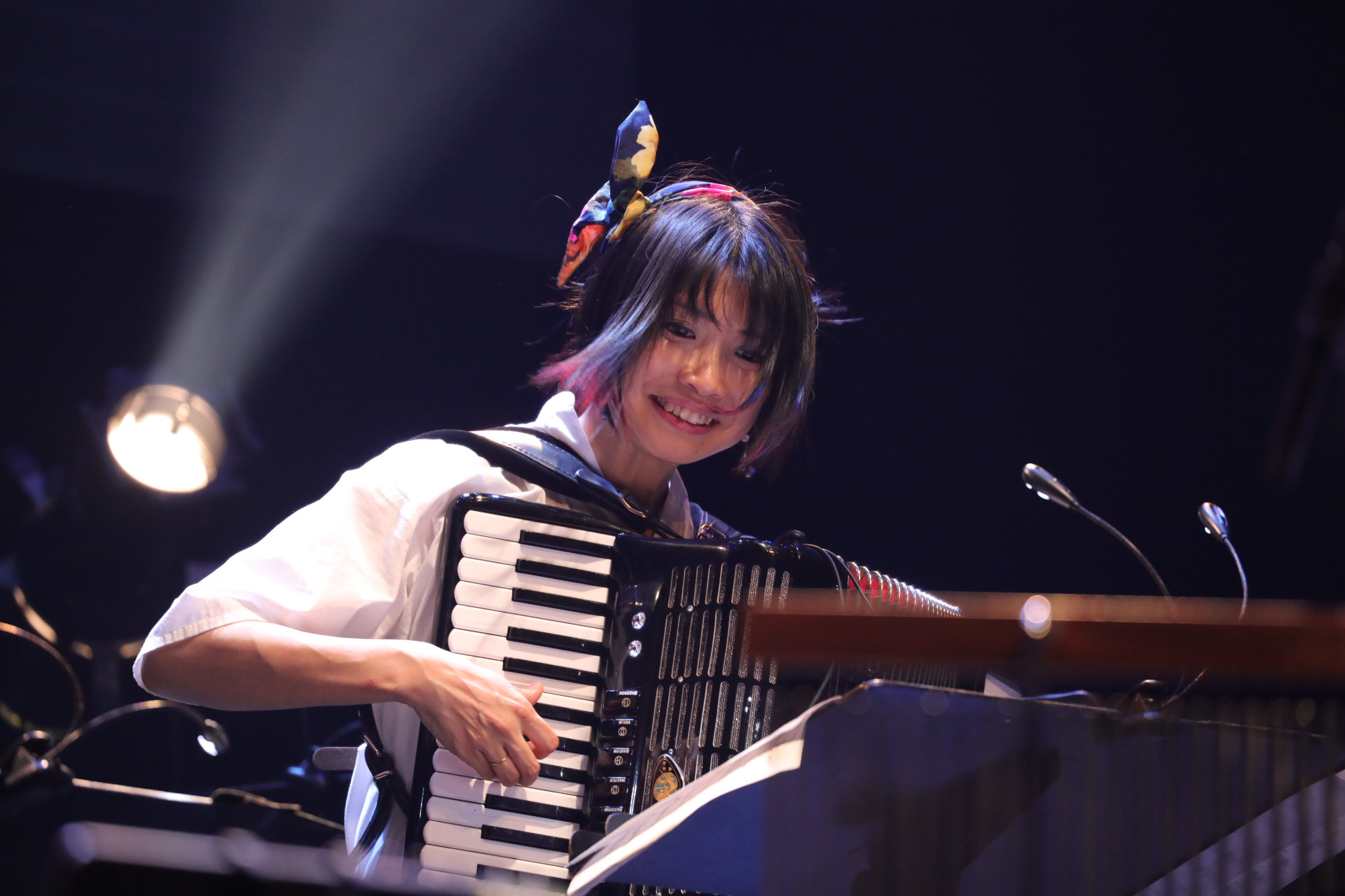 Smiling woman with a colorful headband playing an accordion.