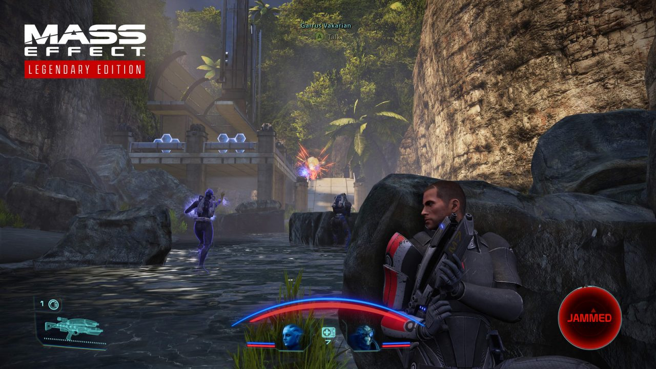 Commander Shepard hides behind a rock as Liara T'Soni uses her biotic powers against a foe in Mass Effect: Legendary Edition.
