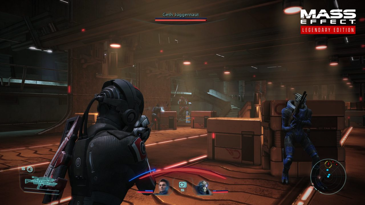 Shepard and Garrus battle the Geth in a warehouse in Mass Effect: Legendary Edition.