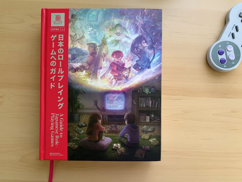The front cover of A Guide to Japanese Role-Playing Games on a flat desk surface with a USB SNES controller in the frame.