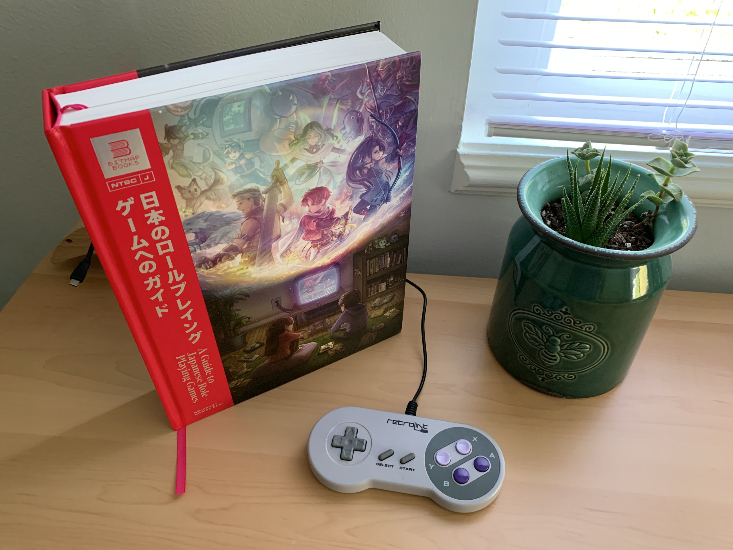 A Guide to Japanese Role-Playing Games by Bitmap Books on a table with an SNES controller and ceramic succulent planter.