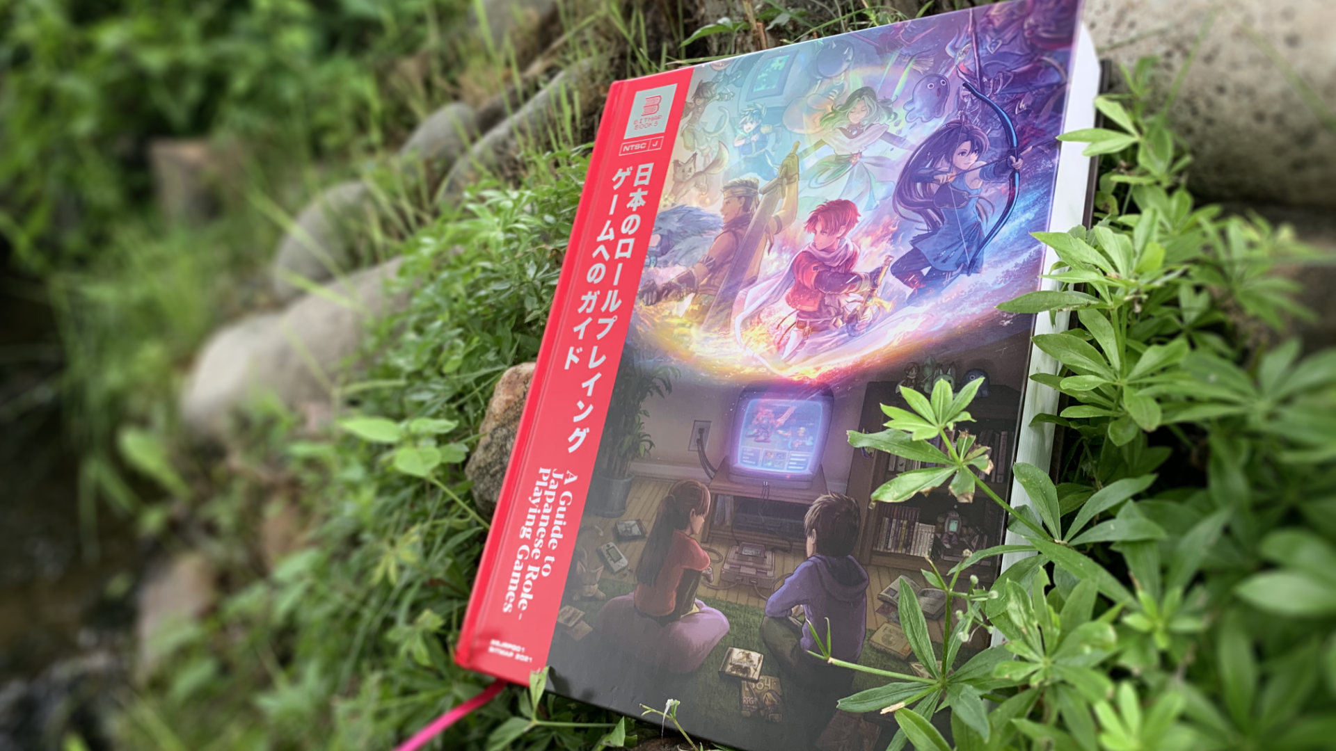 A Guide to Japanese Role-Playing Games against a verdent plant backdrop, with a little stream to the left.