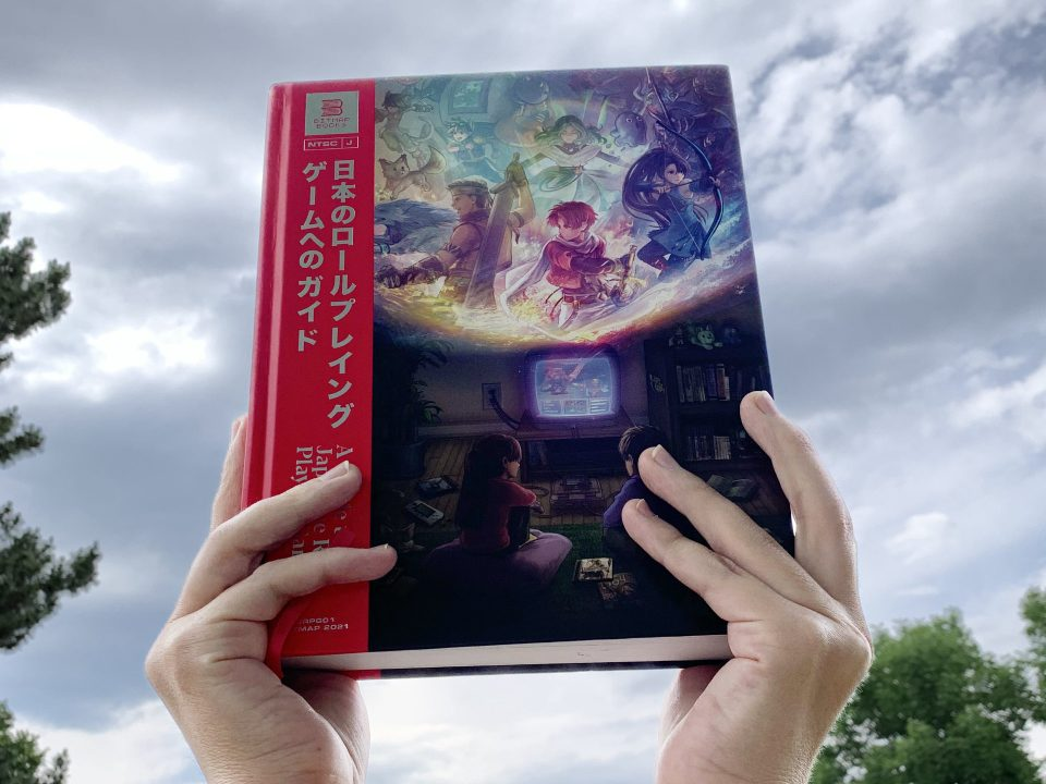 A guide to Japanese Role-Playing Games held aloft Zelda-style with a dramatic sky in the background.