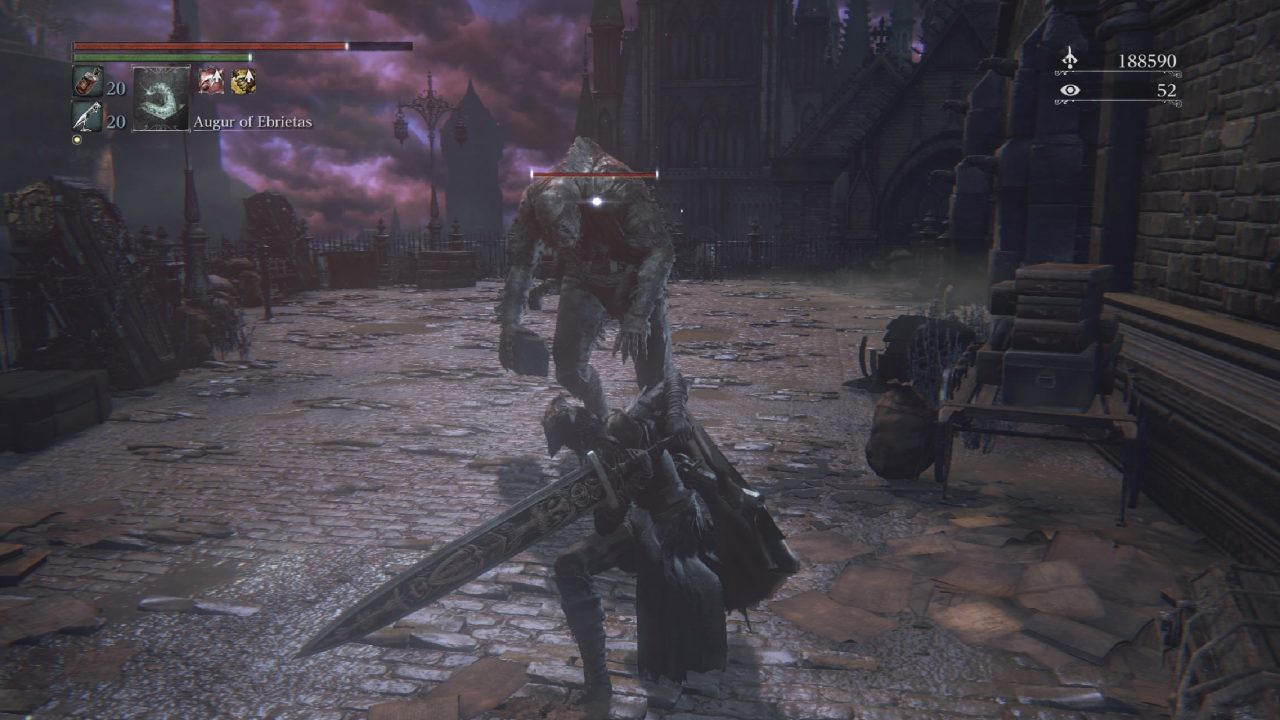 Bloodborne screenshot of a warrior wielding a two-handed greatsword, ready to battle a lumbering humanoid named the Augur of Ebrietas in a gothic castle courtyard.