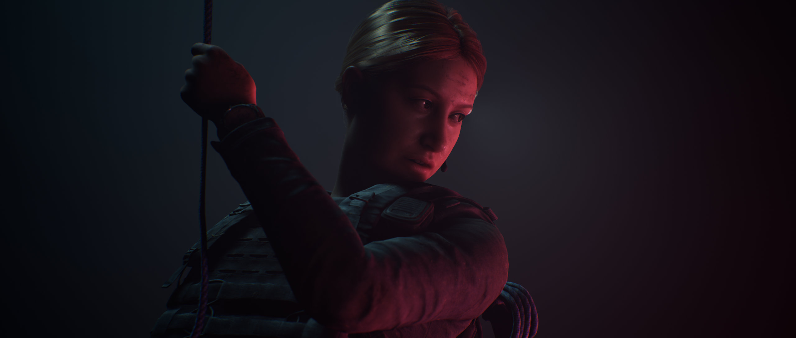 The Dark Pictures Anthology House of Ashes Screenshot of a woman in tactical gear descending a rope into darkness, dimly lit from one side.