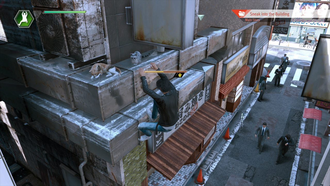 Lost Judgment screenshot of Yagami shimmying across some external air ducts as a few cats look on from above.